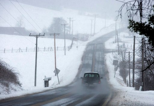 (Erica Yoon /The Roanoke Times via AP). A vehicle drives through snow on Bent Mountain Road near Snake Drive in Copper Hill, Floyd County, Va., Monday, March 12, 2018.