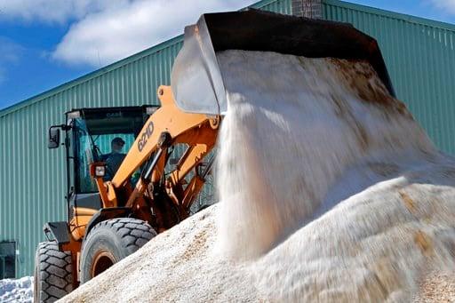 (AP Photo/Robert F. Bukaty). David Osgood, crew leader of the public works dept., mixes road salt, Monday, March 12, 2018, in Freeport, Maine.