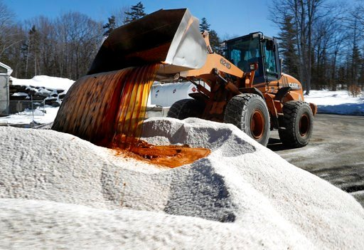 "(AP Photo/Robert F. Bukaty). David Osgood, crew leader of the public works deptartment, mixes ""Ice-B-Gone,"" into a pile of road salt, Monday, March 12, 2018, in Freeport, Maine. The liquid, a by-product of vodka, helps the salt stick to road."