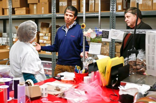 (AP Photo/Keith Srakocic). Republican Rick Saccone, right, and Donald Trump Jr., talk with chocolate workers as they take a tour of Sarris Candies during a campaign stop, Monday, March 12, 2018 in Canonsburg, Pa.