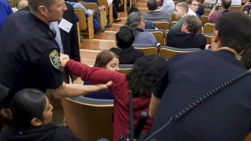 (UCLA via AP). In this image made from a Feb. 26, 2018, video released by the University of California, Los Angeles, a woman is removed from the audience who was listening to U.S. Treasury Secretary Steve Mnuchin speak at UCLA. The previously withheld ...