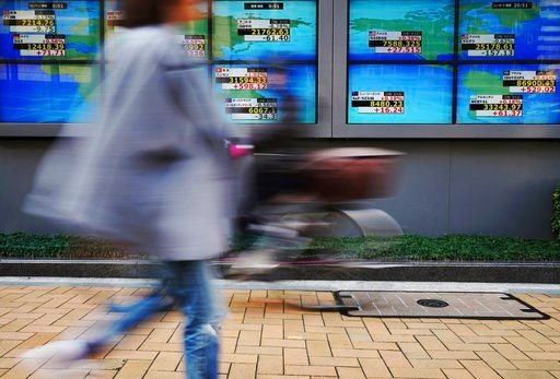 (AP Photo/Eugene Hoshiko). People walk past an electronic stock board showing Japan's Nikkei 225 index and other countries' indexes at a securities firm in Tokyo Tuesday, March 13, 2018. Shares were mixed in Asia on Tuesday following a lackluster day o...