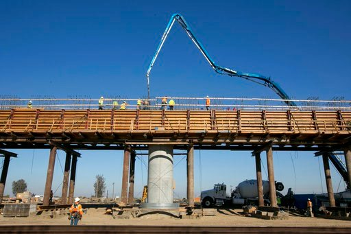 (AP Photo/Rich Pedroncelli, File). In this Dec. 6, 2017, file, workers pour concrete on to one of the elevated sections of the high-speed rail that will cross over the San Joaquin River, near Fresno, Calif.