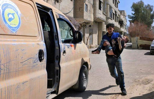 (Syrian Civil Defense White Helmets via AP). This photo released by the Syrian Civil Defense White Helmets, shows a member of the Syrian Civil Defense group carrying a boy who was wounded during airstrikes and shelling by Syrian government forces in Gh...