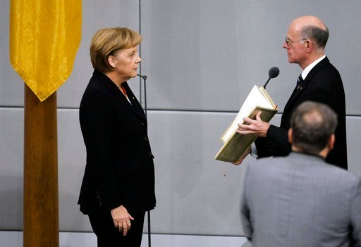 (AP Photo/Markus Schreiber, file). FILE - In this Oct. 28, 2009 file photo reelected German chancellor Angela Merkel, left, takes the oath of office in the parliament in Berlin, Germany. At right is German Parliament President Norbert Lammert. On Wedne...