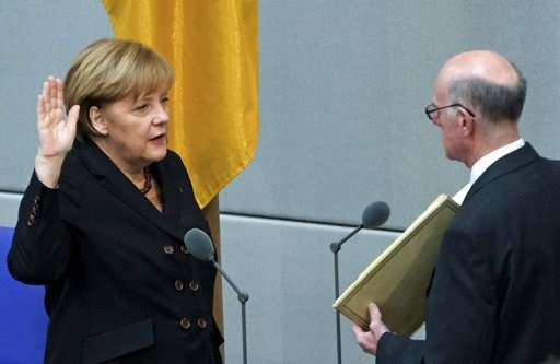 (AP Photo/Jens Meyer, file). FILE - In this Dec. 17, 2013 file photo German Chancellor Angela Merkel, left, takes the oath of office by President of the Federal Parliament, Norbert Lammert during a meeting of the German federal parliament, Bundestag, i...