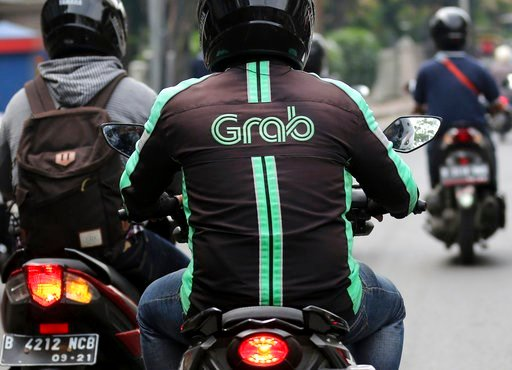(AP Photo/Tatan Syuflana, File). FILE - In this Monday, July 24, 2017, file photo, a GrabBike driver rides on his motorbike in Jakarta, Indonesia. The Southeast Asian ride hailing app Grab is expanding into financial services in partnership with a Japa...