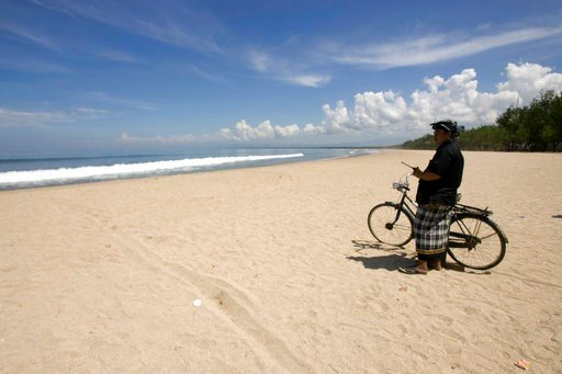 "(AP Photo/Firdia Lisnawati, File). FILE - In this March 16, 2010 file photo, a Balinese traditional security guard called ""pecalang"" patrols the empty Kuta beach, a famous tourist spot on the island, during ""Nyepi"" or the Day of Silence in Bali, Indone..."