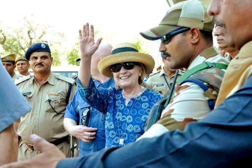 (AP Photo/Sunil Verma). Former U.S. Secretary of State Hillary Clinton, center, waves as she comes out of the Jodhpur airport upoon her arrival in Jodhpur, Rajasthan state, India, Tuesday, March 13, 2018.