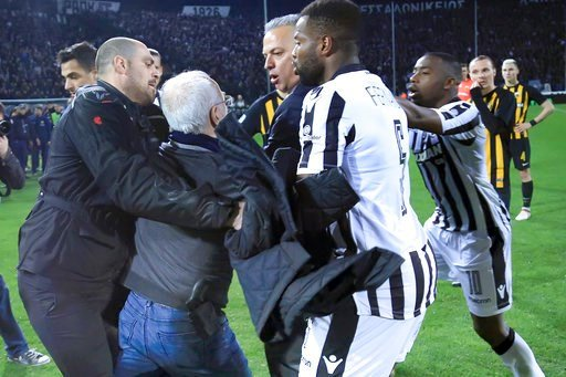 (InTime Sports via AP). PAOK owner, businessman Ivan Savvidis, second from left, approaches AEK Athens' Manager Operation Department Vassilis Dimitriadis, center, as his bodyguard and PAOK's players Fernando Varela, second from right, and Djalma Campos...