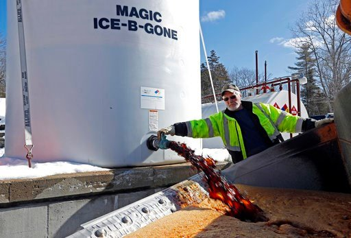 "(AP Photo/Robert F. Bukaty). David Osgood, crew leader of the public works dept., fills the bucket of a front-end loader with ""Ice-B-Gone,"" Monday, March 12, 2018, in Freeport, Maine. The liquid, a by-product of vodka, is mixed with road salt stick for..."