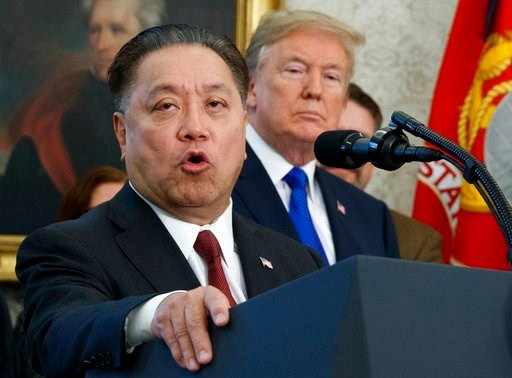 (AP Photo/Evan Vucci, File). FILE - In this Thursday, Nov. 2, 2017, file photo, Broadcom CEO Hock Tan speaks while U.S. President Donald Trump listens, in background, during an event at the White House in Washington, to announce the company is moving i...