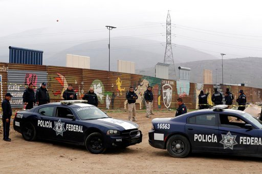 (AP Photo/Gregory Bull). Mexican federal police officers stand guard on the Mexico side of the border on Tuesday, March 13, 2018, in Tijuana, Mexico. President Trump is scheduled to visit the site of the border wall prototypes which can be seen in the ...