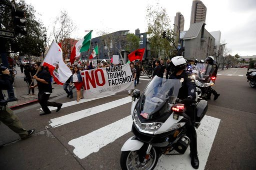 (AP Photo/Gregory Bull). People march during a rally against a scheduled upcoming visit by President Donald Trump, Monday, March 12, 2018, in San Diego. Trump is scheduled to visit San Diego on Tuesday, setting foot in California for his first time as ...