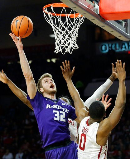 (AP Photo/Garett Fisbeck, File). FILE - In this Feb. 24, 2018, file photo, Kansas State's Dean Wade (32) takes a shot against Oklahoma's Christian James (0) and Khadeem Lattin (3) during the first half of an NCAA college basketball game, in Norman, Okl...