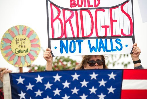 "(AP Photo/Kyusung Gong). Lauren Rees holds up a sign during a rally against a upcoming scheduled visit by President Donald Trump Tuesday, March 13, 2018, in San Diego.  Protesters chanted, ""No ban! No wall!"" near the San Ysidro border crossing, where t..."