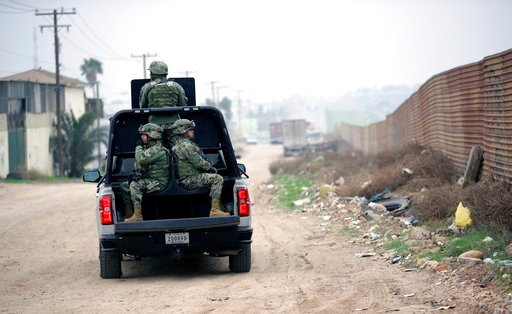 (AP Photo/Gregory Bull). Mexican Navy officers patrol on the Mexico side of the border on Tuesday, March 13, 2018, in Tijuana, Mexico. President Trump is scheduled to visit the site of the border wall prototypes which are on the U.S. side of the wall s...