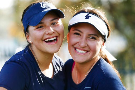 (AP Photo/Damian Dovarganes). In this Monday, March 12, 2018, Bella Marez, left, and Katrina Yuzefpolsky pose for a photograph after practice with their high school softball team in Pasadena, Calif. Katrina was 8 years old when a man dressed as Santa s...