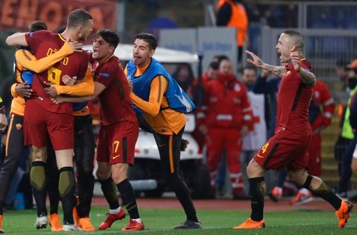 (AP Photo/Gregorio Borgia). Roma's Edin Dzeko, left, celebrates with teammates after scoring his side's opening goal during a Champions League round of 16 second-leg soccer match between Roma and Shakhtar Donetsk, at the Rome Olympic stadium, Tuesday, ...