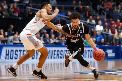 (AP Photo/John Minchillo). LIU Brooklyn's Julian Batts, right, drives against Radford's Carlik Jones during the first half of a First Four game of the NCAA men's college basketball tournament, Tuesday, March 13, 2018, in Dayton, Ohio.