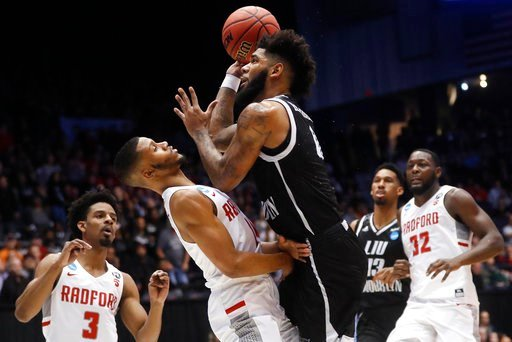 (AP Photo/John Minchillo). LIU Brooklyn's Joel Hernandez, center right, shoots against Radford's Travis Fields Jr. during the first half of a First Four game of the NCAA men's college basketball tournament, Tuesday, March 13, 2018, in Dayton, Ohio.