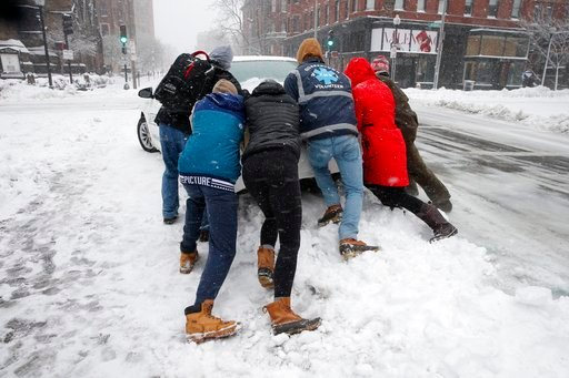 (AP Photo/Michael Dwyer). People push a stranded taxi during a snowstorm, Tuesday, March 13, 2018, in Boston.