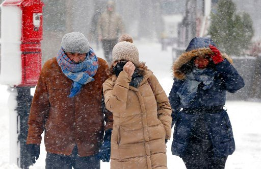 (AP Photo/Michael Dwyer). Pedestrians make their way through blowing snow during a snowstorm, Tuesday, March 13, 2018, in Boston.