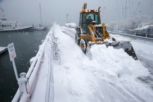 (AP Photo/Michael Dwyer). A front end loader clears the pier at the Boston Harbor Shipyard and Marina in Boston, Tuesday, March 13, 2018.