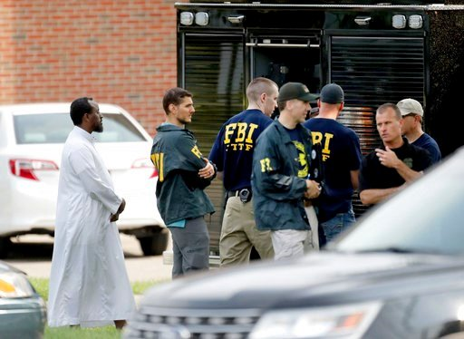 (David Joles/Star Tribune via AP File). FILE - In this Aug. 15, 2017 file photo, Law enforcement officials investigate an explosion at the Dar Al-Farooq Islamic Center in Bloomington, Minn. Federal authorities said Tuesday, March 13, 2018, they have ch...