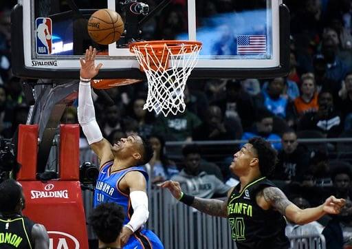 (AP Photo/John Amis). Oklahoma City Thunder guard Russell Westbrook shoots a reverse layup as Atlanta Hawks forward John Collins (20) defends during the first half of an NBA basketball game, Tuesday, March 13, 2018, in Atlanta.
