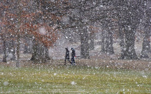 (Darrell Sapp/Pittsburgh Post-Gazette via AP). People cross Flagstaff Hill as the snow starts to fall, in Schenley Park, on their way to the Carnegie Mellon University campus, Tuesday, March 20, 2018, in the Oakland section of Pittsburgh. Yet another p...
