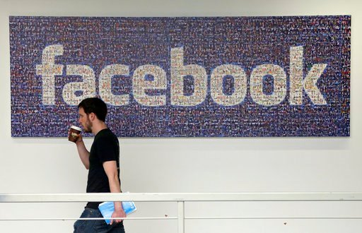 (AP Photo/Jeff Chiu, File). FILE - In this March 15, 2013, file photo, a Facebook employee walks past a sign at Facebook headquarters in Menlo Park, Calif. The San Jose Mercury News reports Saturday, March 17, 2018 that building permits compiled by Bui...