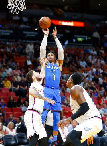 (AP Photo/Wilfredo Lee). Oklahoma City Thunder guard Russell Westbrook (0) shoots against Miami Heat guard Tyler Johnson, left, and center Hassan Whiteside (21) during the first half of an NBA basketball game, Monday, April 9, 2018, in Miami.
