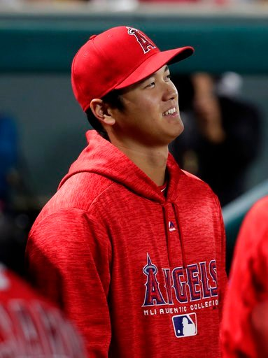 (AP Photo/Tony Gutierrez). Los Angeles Angels' Shohei Ohtani smiles as he talks with teammates in the dugout during the third inning of a baseball game against the Texas Rangers in Arlington, Texas, Monday, April 9, 2018.