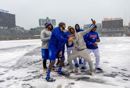 (Brian Cassella/Chicago Tribune via AP). Chicago Cubs' Kris Bryant, left foreground, and Carl Edwards Jr., right foreground, pose for a selfie with teammates in the snow at Wrigley Field in Chicago, Monday, April 9, 2018. The Cubs baseball game against...