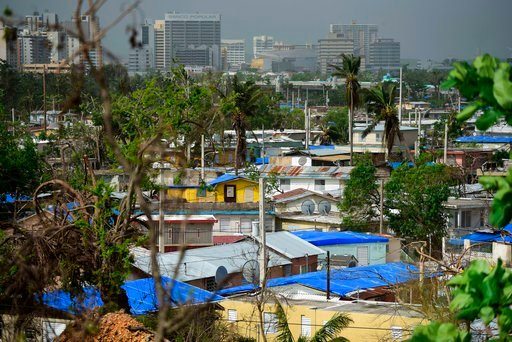 (AP Photo/Carlos Giusti, File). FILE - In this Oct. 19, 2017, file photo, homes stand covered with FEMA tarps in the Cantera area, as the banking zone stands in the background in San Juan, Puerto Rico. The Federal Emergency Management Agency awarded co...