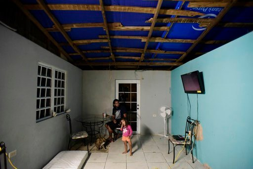 (AP Photo/Carlos Giusti). FILE - In this Dec. 21, 2017, file photo, two year old Yeinelis Oliveras González accompanies her father, Luis Oliveras, while eating dinner, in Morovis, Puerto Rico. The light blue glow cast by a tarp that covers half their r...