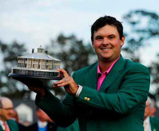 (AP Photo/David J. Phillip). Patrick Reed holds the championship trophy after winning the Masters golf tournament Sunday, April 8, 2018, in Augusta, Ga.