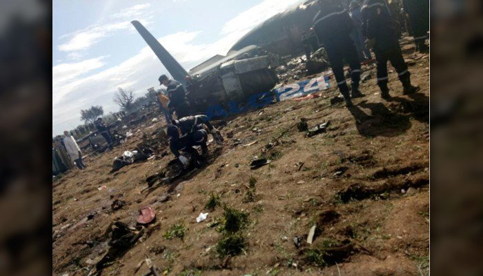 Firefighters and soldiers are shown at the scene of a fatal military plane crash near Boufarik military base near the Algerian capital, Algiers. (ALG24 via AP)