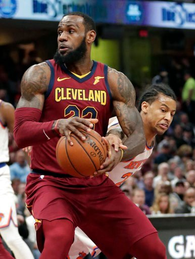 (AP Photo/Tony Dejak). Cleveland Cavaliers' LeBron James, left, drives past New York Knicks' Trey Burke in the first half of an NBA basketball game, Wednesday, April 11, 2018, in Cleveland.