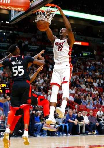 (AP Photo/Wilfredo Lee). Miami Heat center Bam Adebayo (13) dunks in front of Toronto Raptors guard Delon Wright (55) and guard Kyle Lowry, left rear, during the second half of an NBA basketball game Wednesday, April 11, 2018, in Miami. The Heat won 11...