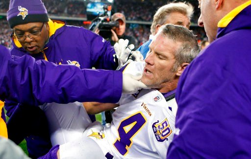 (AP Photo/Michael Dwyer, File). FILE - In this Oct. 31, 2010, file photo, Minnesota Vikings quarterback Brett Favre, center, is helped onto a cart to be taken off the field after a hit from New England Patriots' Myron Pryor during the fourth quarter of...
