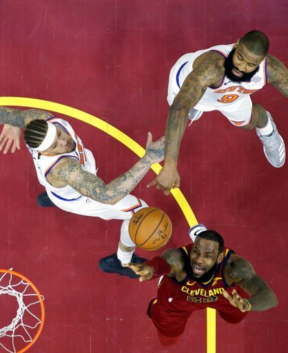 (AP Photo/Tony Dejak). Cleveland Cavaliers' LeBron James, bottom, drives to the basket against New York Knicks' Michael Beasley, left, and Kyle O'Quinn in the first half of an NBA basketball game, Wednesday, April 11, 2018, in Cleveland.