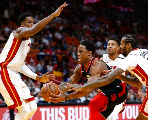 (AP Photo/Wilfredo Lee). Toronto Raptors guard DeMar DeRozan, center, drives to the basket against Miami Heat center Hassan Whiteside, left, guard Rodney McGruder, rear, and forward James Johnson, right, during the first half of an NBA basketball game ...