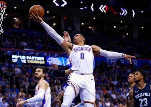 (AP Photo/Sue Ogrocki). Oklahoma City Thunder guard Russell Westbrook (0) goes to the basket in front of Memphis Grizzlies forward Dillon Brooks, rear, and guard Ben McLemore (23) and Thunder's Steven Adams, left, during the second half of an NBA baske...