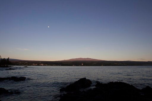 (AP Photo/Caleb Jones, File). FILE - This Aug. 31, 2015 file photo shows Mauna Kea, Hawaii's tallest mountain and the proposed construction site for a giant $1.4 billion telescope project, as seen from Hilo, Hawaii. On Friday, April 13, 2018, officials...