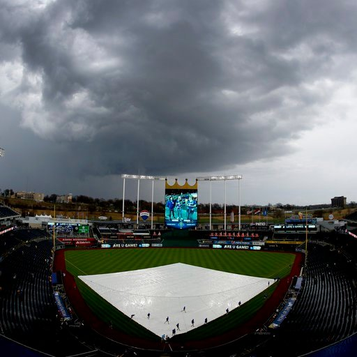 (AP Photo/Charlie Riedel). Grounds crew workers pull the tarp off the field after a storm dumped rain on Kauffman Stadium before a baseball game between the Kansas City Royals and the Los Angeles Angels ,Friday, April 13, 2018, in Kansas City, Mo.