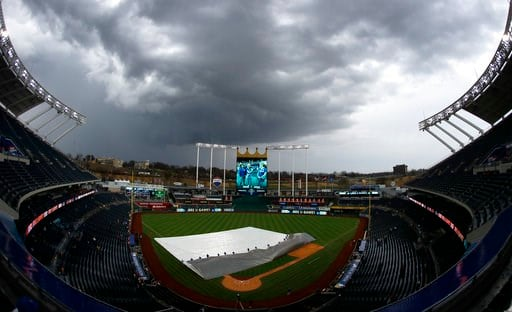 (AP Photo/Charlie Riedel). Grounds crew workers pull the tarp off the field after a storm dumped rain on Kauffman Stadium before a baseball game between the Kansas City Royals and the Los Angeles Angels, Friday, April 13, 2018, in Kansas City, Mo.