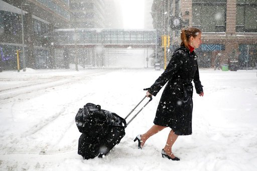 (Anthony Souffle/Star Tribune via AP). Delta Airlines flight attendant Victoria Flees trudges through the snow with her bags in downtown Minneapolis on the way back home from the light rail station after her flight to Paris was grounded.