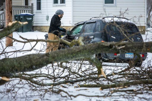 (Joe Ahlquist/The Rochester Post-Bulletin via AP). Lee Rinehart scrapes snow and ice off of his vehicle near where a large tree branch had fallen during a storm Saturday, April 14, 2018, in Rochester, Minn.